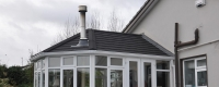 Black tiled roof conservatory with a chimney