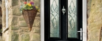Black front door with chrome hardware and decorative glass