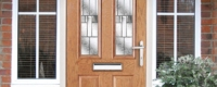 Front door in oak woodgrain colour with chrome handle and letterplate
