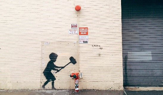 Banksy art on cream brick wall